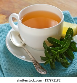 Cup of  herbal tea  with lemon on wooden background