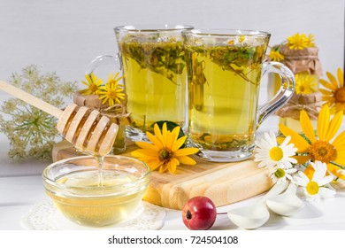 Cup of herbal tea with natural light liquid honey  and wild flowers on white background