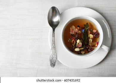 A cup with herbal tea, a plate and a teaspoon on a wooden background
