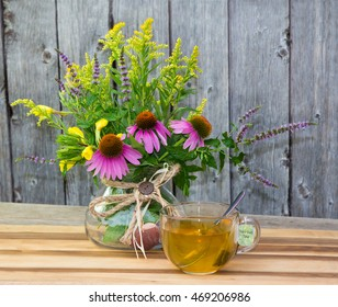 Cup of herbal tea from solidago and echinacea on wooden background.