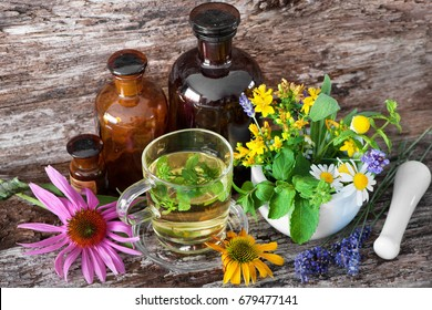 Cup of herbal tea with tincture bottles and healing herbs in mortar on wooden table
