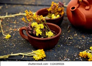 Cup of herbal tea - tutsan, sagebrush, oregano, helichrysum, lavender near brown teapot on dark wooden background. Herbal tea. Dry Herbs and flowers, herbal medicine.