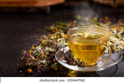 Cup of herbal tea with various herbs on dark background