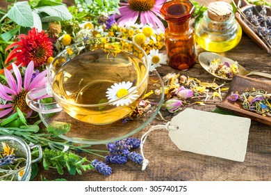 Cup of herbal tea with wild flowers, honey and empty tag