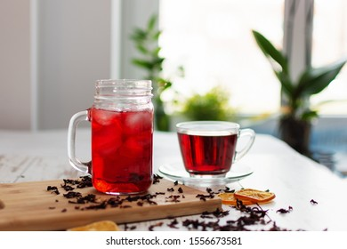 Cup of hibiscus tea (karkade, red sorrel, Agua de flor de Jamaica) on a table. Drink made from magenta calyces (sepals) of roselle flowers.