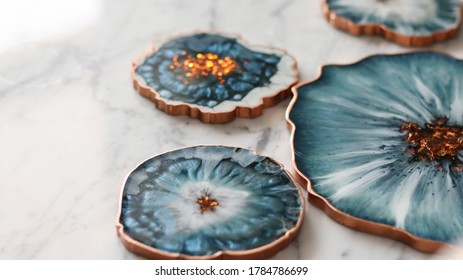 Cup holder, epoxy resin tray, marine-style stone cut. Blue stains of paint, gold trim. Subject for table setting. Gloss, reflection.