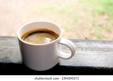 Cup of hot americano at window in morning. Art of coffee and cafeine.
