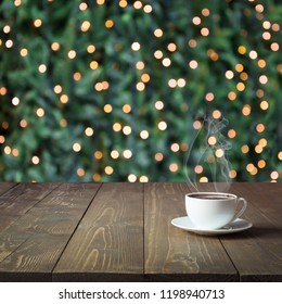 Cup of hot black coffee on wooden table in cafe. Blurred gold garland as background. Christmas Time. Image for display your christmas products.