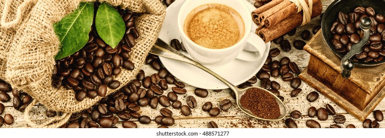 Cup of hot black coffee in retro setting with old wooden mill grinder and burlap sack with roasted coffee beans. Copy space