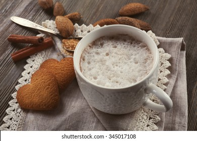Cup of hot cacao on cotton serviette with cinnamon, almonds and heart shaped cookies