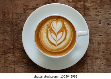 Cup of hot cappuccino coffee with beautiful latte art on wooden table background