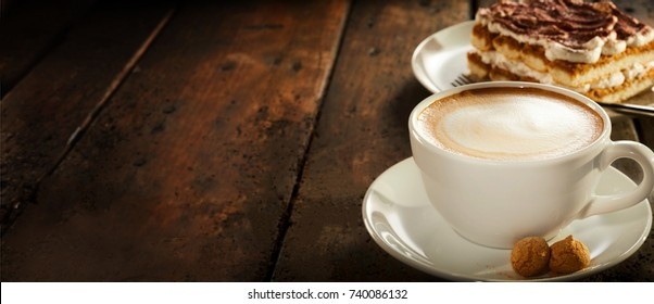 Cup of hot cappuccino coffee with cake on a rustic wooden table with copy space in banner format