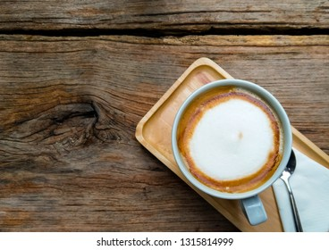 A cup of hot cappuccino coffee on wooden background.