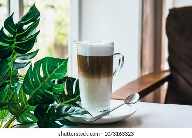 A cup of Hot cappuccino latte coffee with cinnamon sprinkles on top on wooden white dinner table with a green leaf in a  background