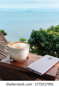 A cup of hot cappuchino and cell phone on wooden brown board over seascape background. Fresh coffee and good morning concept.