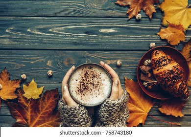 Cup of hot cappuchino coffee with chocolate croissant, Autumn mood, holding hands, top view , warm and cozy