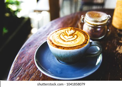 Cup of hot cappucino is on wooden table background. hippster style