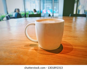 a cup of hot capuchino on wood in coffee shop