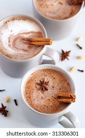 Cup of hot chai latte with spices like cinnamon, cardamon, cloves, star anise as a sweet warm winter dessert drink