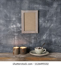 Cup of hot chocolate and burning candles on distressed wooden table against rough plaster grey wall with shabby frame.