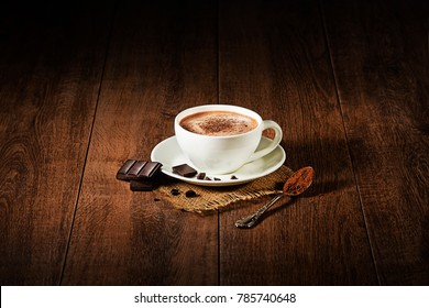 Cup of hot chocolate and cappuccino on wooden background.