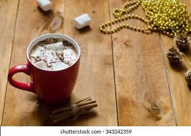 cup of hot chocolate with cinnamon and marshmallows on wooden background