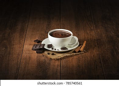 Cup of hot chocolate and cocoa on wooden background.