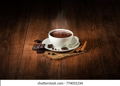 Cup of hot chocolate and cocoa with smoke on wooden background.