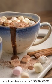 Cup of hot chocolate drink with marshmallows and cinnamon on brown wooden background.