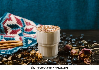 Cup of hot chocolate, latte, cappucino, on wooden table with blueberries, cinnamon. Cup of coffee with different spices and dry roses background. Holiday/ Christmas concept.