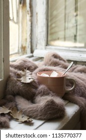 Cup of hot chocolate with marhmallow, warm soft sweater and fall leaves on vintage wooden windowsill. Cozy autumn still life.