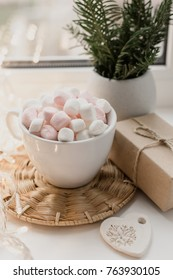 Cup of hot chocolate and marshmallow in the background of Christmas decorations.