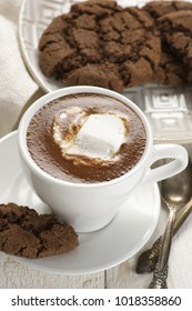 Cup of hot chocolate with marshmallow and chocolate crinkle cookies in plate on white wooden table.