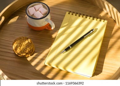 Cup of hot chocolate with marshmallow and notebook with to do list on wooden background