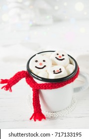 Cup with hot chocolate and marshmallow snowman faces on a white background, christmas drink