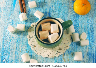 A cup of hot chocolate with marshmallows and gingerbread on a Christmas table.