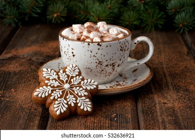 Cup of hot chocolate with marshmallows and gingerbread cookies on a wooden table