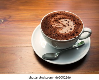 Cup of hot chocolate on wood table background.