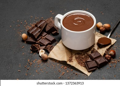 Cup of hot chocolate and pieces of chocolat on dark concrete background