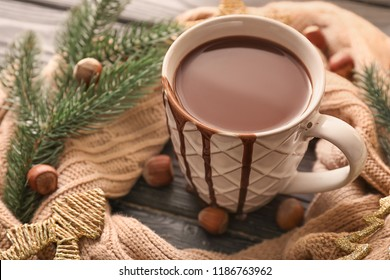 Cup of hot chocolate with warm scarf on wooden table