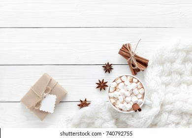 Cup of hot chocolate and white scarf on a white table before christmas eve