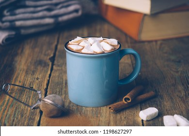 Cup of hot cocoa or hot chocolate with marshmallows and cinnamon sticks on wooden background. Winter mood.