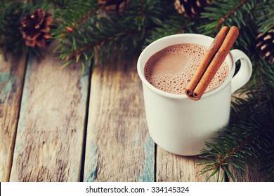 Cup of hot cocoa or hot chocolate on wooden background with fir tree and cinnamon sticks, traditional beverage for winter time, vintage toning.
