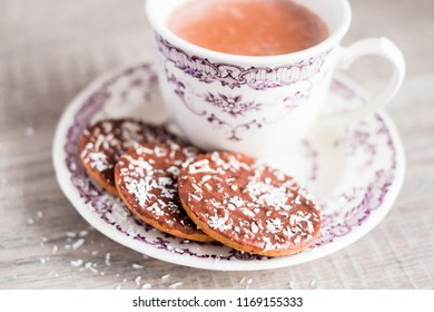 Cup of hot cocoa drink or hot chocolate with vanilla cookies coated in milk chocolate and sprinkled with freshly shredded coconut on a dessert plate on a wooden table, selective focus. Christmas.