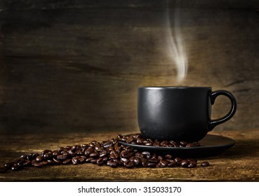 Cup of hot coffee and coffee beans on old wood background