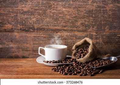 A cup of hot coffee, coffee beans on the stainless scoop and coffee bag on the wooden table, morning time, soften by window light, coffee concept