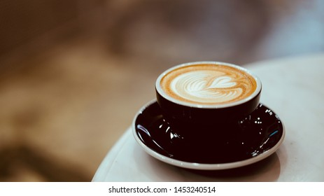 cup of hot coffee with beautiful heart shape latte art with copy space on left, vintage tone