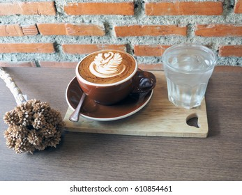 Cup of hot coffee with beautiful latte art served with glass of iced drinking water on wooden tray