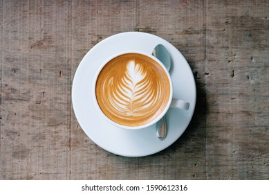 Cup of hot coffee cappuccino on wooden table