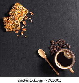 Cup of hot coffee and cookies with nuts, sesame and sunflower seeds on black stone background, top view